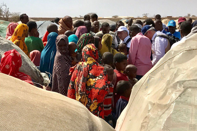Photo: Families displaced by drought in Baidoa, Somalia, gather around Secretary-General António Guterres (white cap), who was in the region urging action to help them. Photo: UNSOM