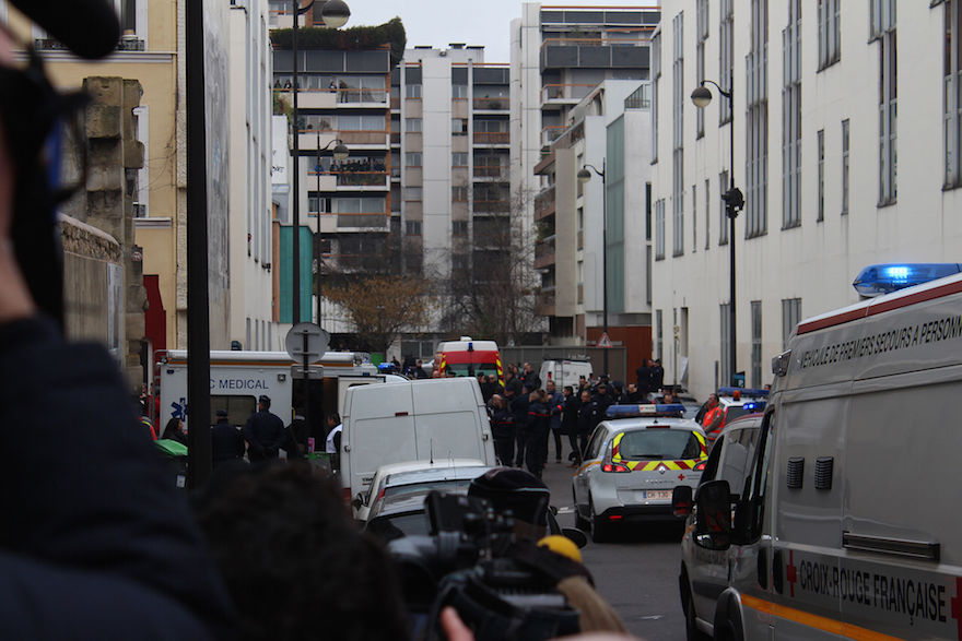 Journalists, policemen, and emergency services in the street of the shooting, a few hours after the January 2015 attack. Credit: Wikimedia Commons