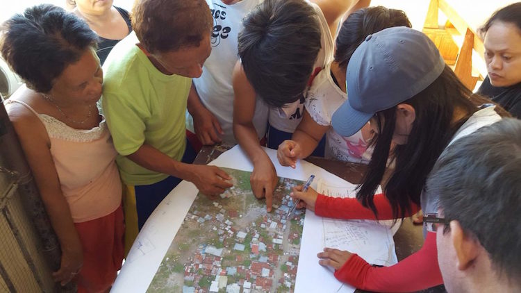Photo: Of the 24 million land parcels that exist in the Philippines, it is estimated that only half have formal land titles. Here, community members examine aerial maps from a drone survey. Credit: Asia Foundation