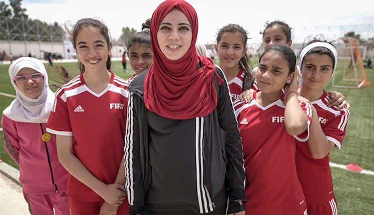 Photo: Syrian refugee and Jordanian girls participate in a mixed-nationality football camp in Jordan. Photo: UN Women/Christopher Herwig