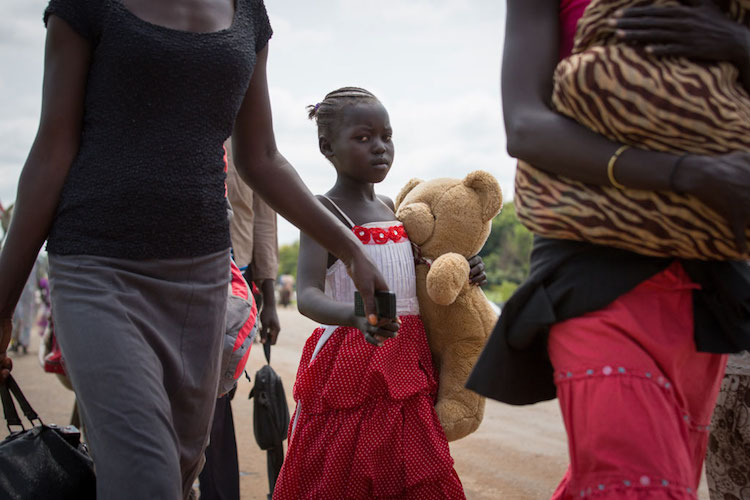 Photo: A young refugee and her family cross the border between South Sudan and Uganda. Photo: UNHCR/Will Swanson