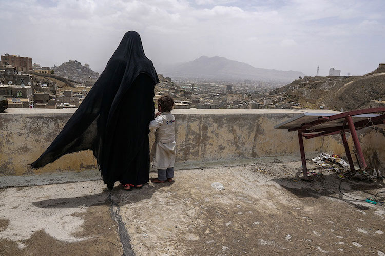 Photo: An internally displaced woman and her daughter look over the city of Sana'a, Yemen, from the roof of this dilapidated building they call their new home. Photo: Giles Clarke/UN OCHA
