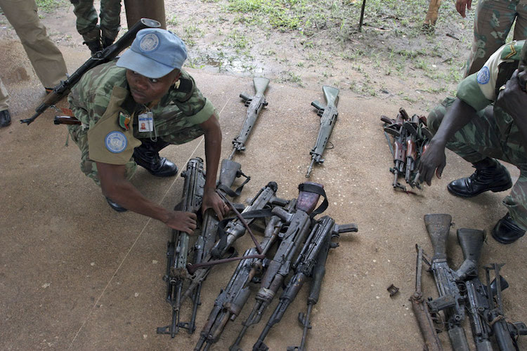 Photo: A UN peacekeeper with firearms collected from militias in Côte d'Ivoire. UN Photo/Ky Chung