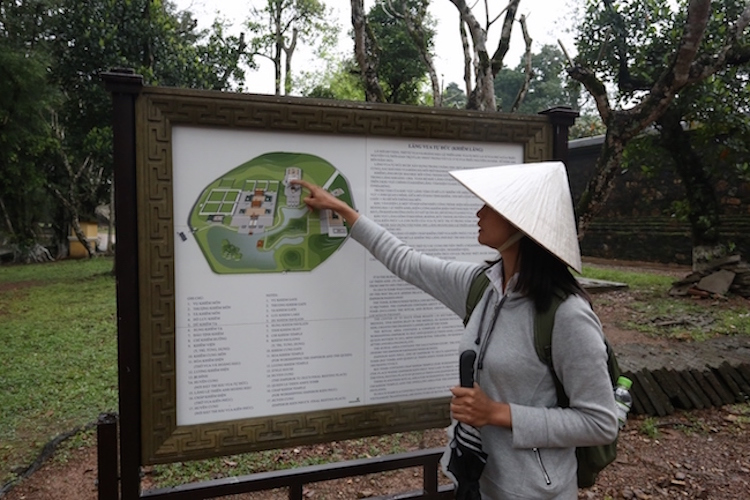Photo: Pham Thi Kim Viet, a tour guide, shows visitors the map of Huế, a city in central Vietnam which was the seat of the Nguyen Dynasty emperors. Credit: Neena Bhandari.