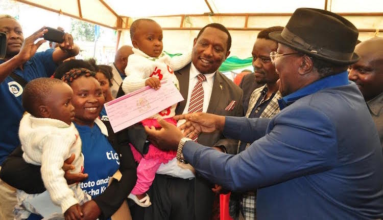 Photo: Tanzania's Minister for Justice and Constitutional Affairs Harrison Mwakyembe hands over a birth certificate to a two years old Justine Masawe during a handover ceremony in Njombe early in October 2015. Credit: Kizito Makoye | IDN-INPS